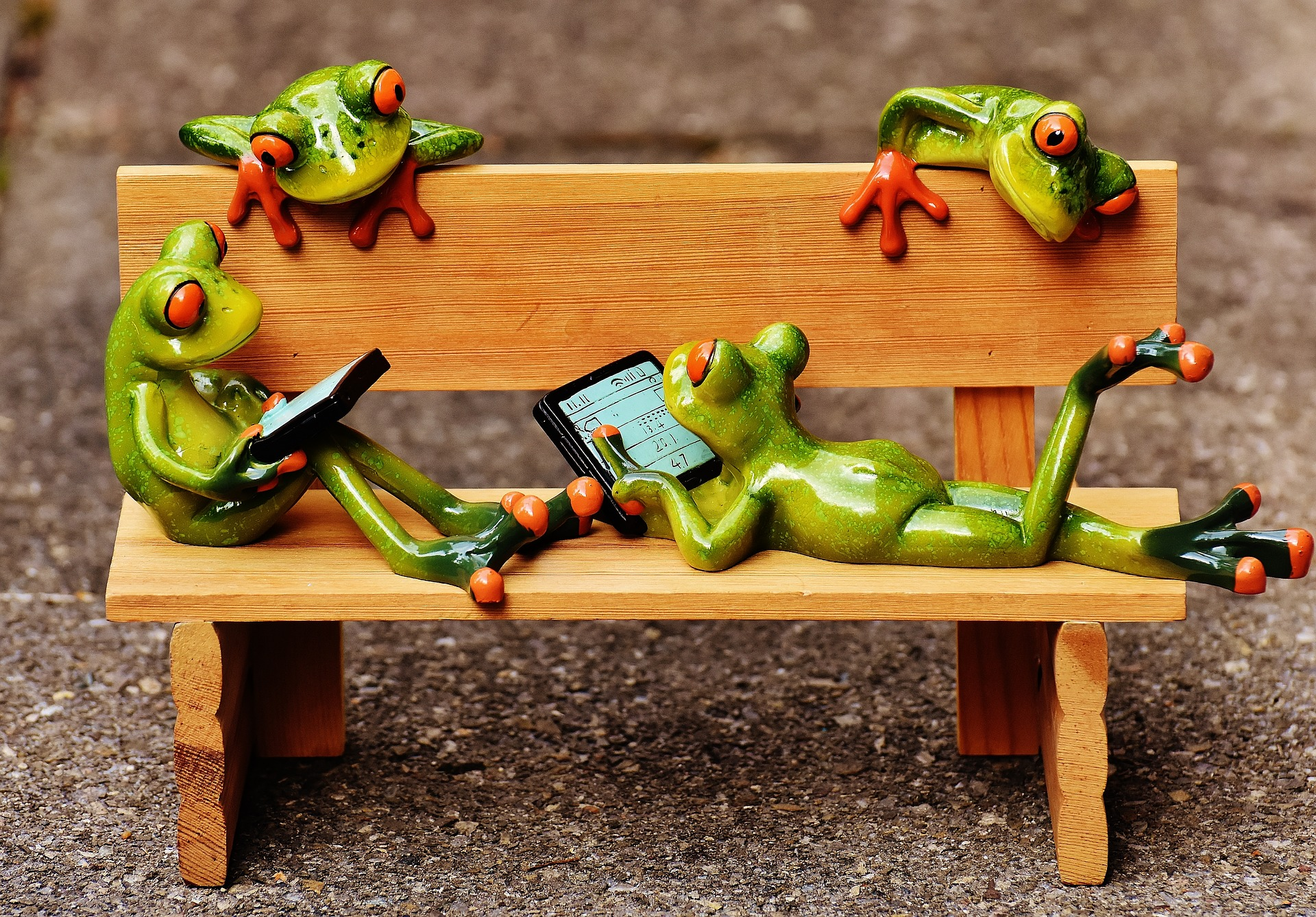 Frogs on a bench with laptops and tablet computers