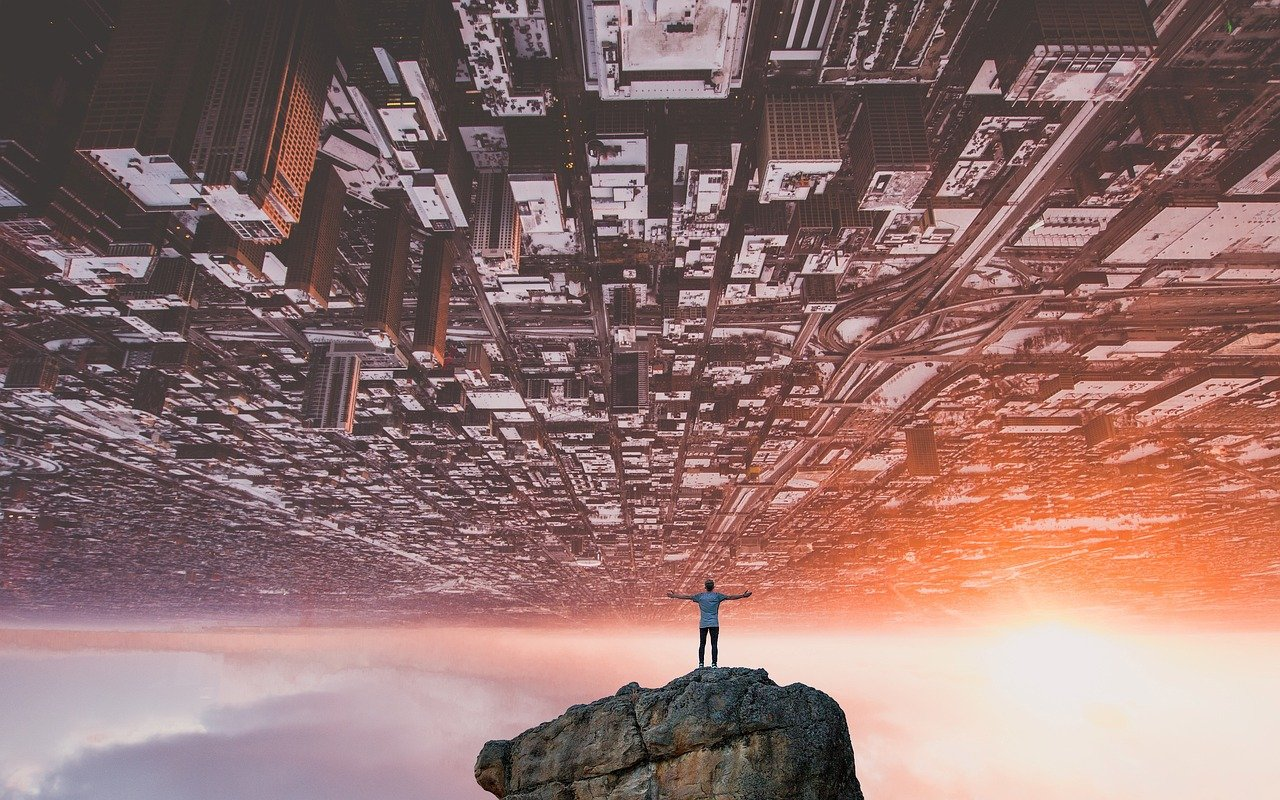 Inverted futuristic cityscape with a man in a rock