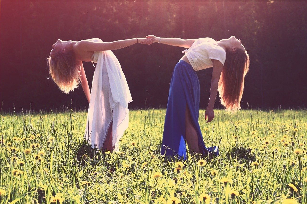 Two women holding hands in a sunny grass field