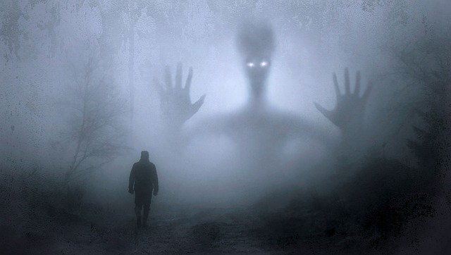 Foggy image of a monster with a man in the foreground